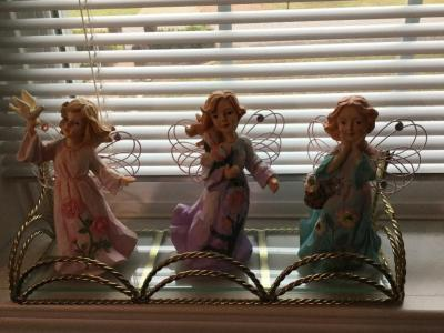 Glass shelf with three angel girls statues
